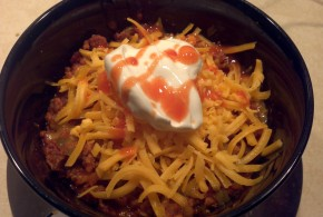 Caveman Chili topped with cheese, sour cream and frank's red hot